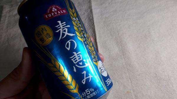 トップバリュ「麦の恵み」の缶を持っているところ